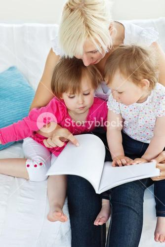 Glowing family reading a book on the sofa
