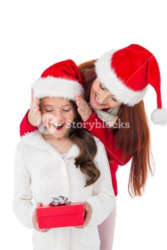 Festive mother surprising daughter with gift