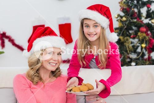 Festive mother and daughter with plate of cookies