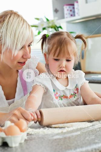Attentive young mother baking with her daughter