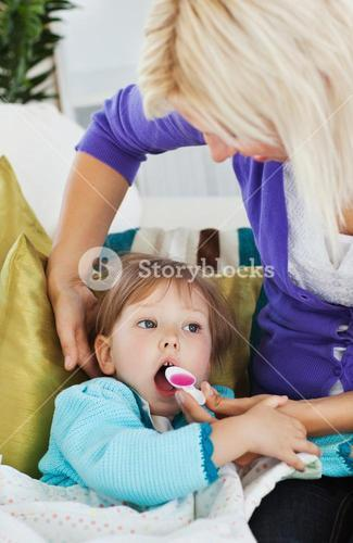 Sick little girl getting syrup from her caring mother