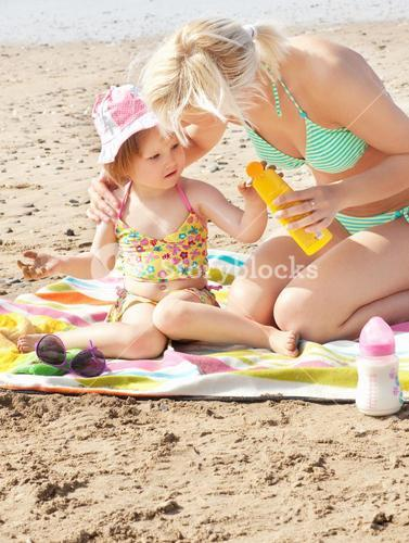 Attentive mother at the beach with her daughter