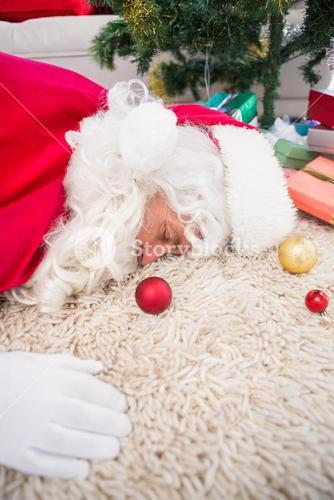 Exhausted santa sleeping on the rug