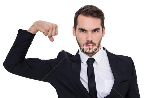Businessman tensing arm muscle and looking at camera