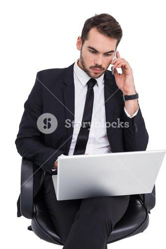 Businessman using laptop while phoning