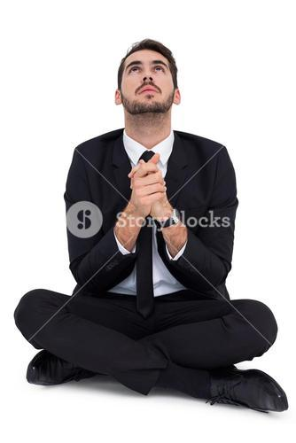 Businessman sitting praying and looking up