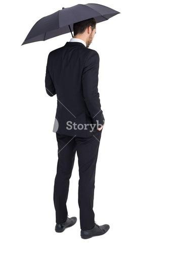 Thoughtful businessman under umbrella with hand in pocket