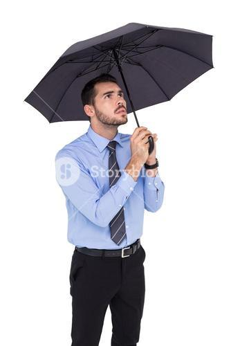Anxious businessman sheltering with umbrella