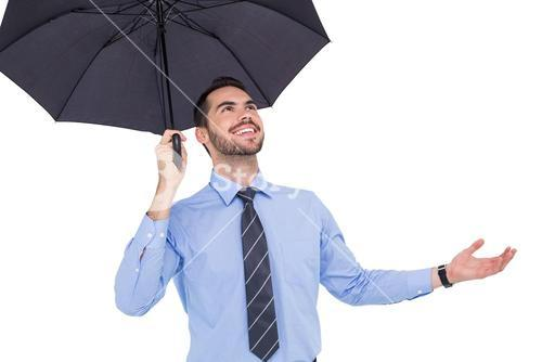 Happy businessman sheltering with a black umbrella