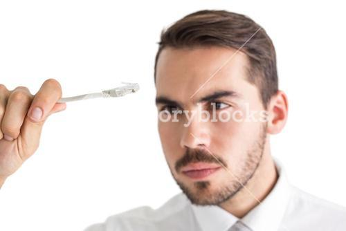 Focused businessman holding white cable