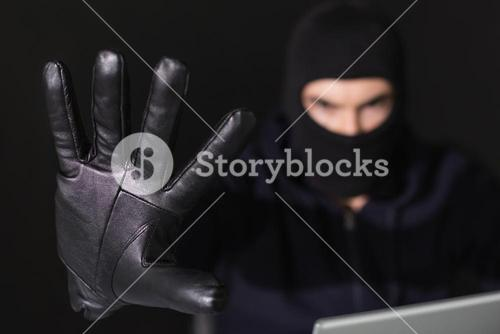 Hacker in balaclava with fingers spread out