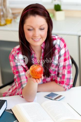 Positive student with an apple at home