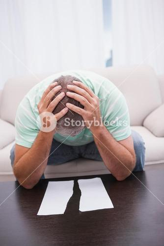 Worried man looking at ripped page