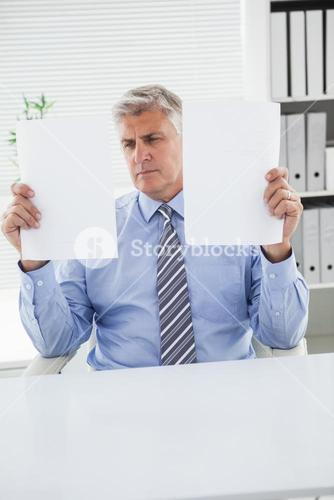 Mature businessman looking at two pages