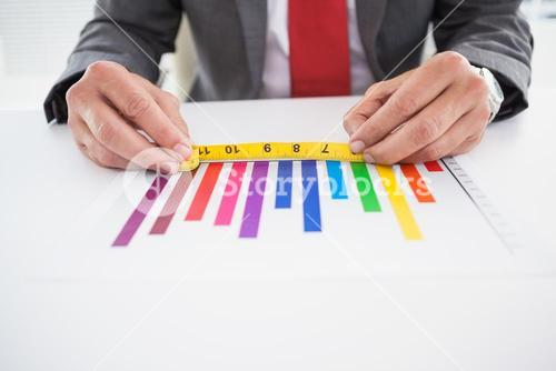 Businessman measuring graph with tape