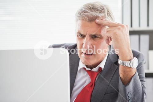 Confused businessman looking at his laptop
