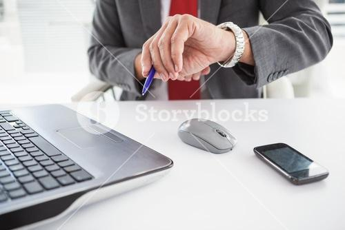 Mature businessman checking the time