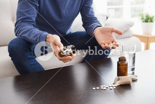 Man with his medicine laid out on coffee table