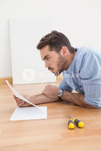 Casual man reading instruction manual for power tool