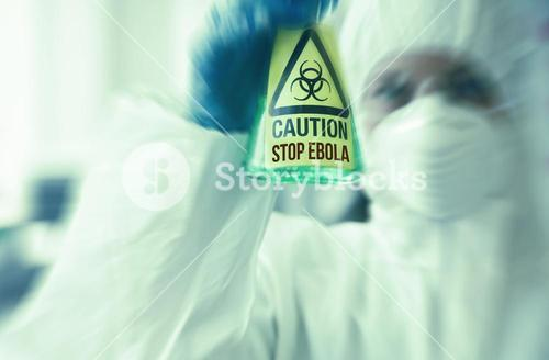 Scientist in protective suit holding beaker