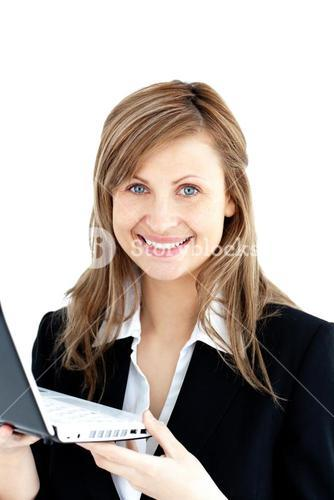 Confident businesswoman holding a laptop smiling at the camera