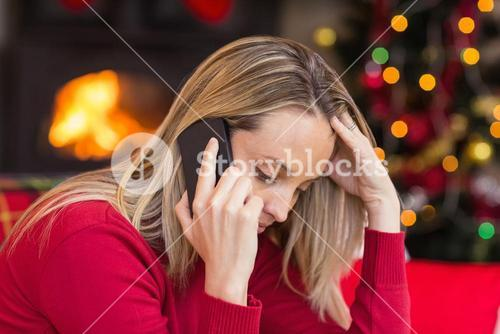 Upset young woman looking down while calling on phone