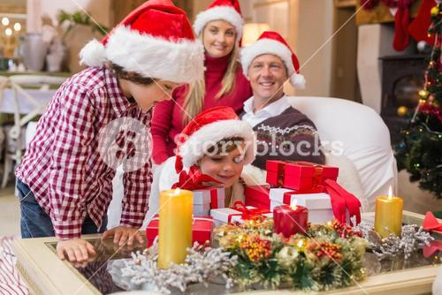 Smiling family at christmas time with lots of presents