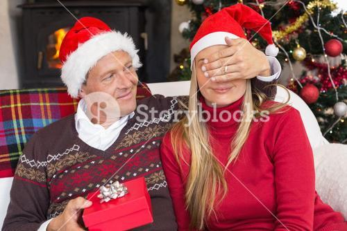 Man covering partner eyes and offering a gift to her