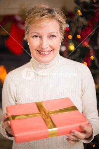 Smiling active seniors holding a gift at christmas