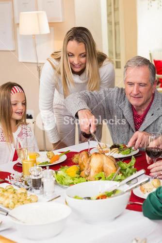 Grandfather carving chicken during christmas dinner