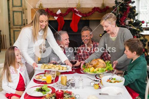 Two women serving christmas dinner to their family