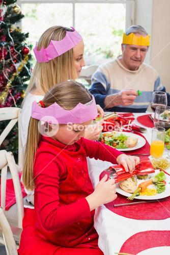Little girl in party hat holding christmas crackers