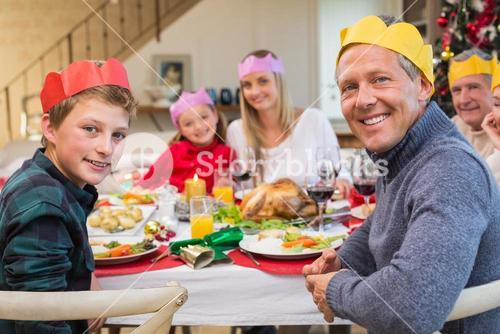 Smiling extended family in party hat at dinner table