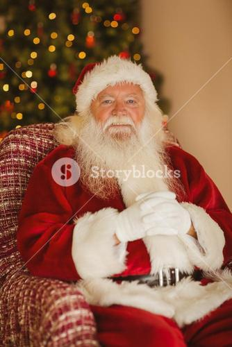 Happy santa relaxing on the armchair