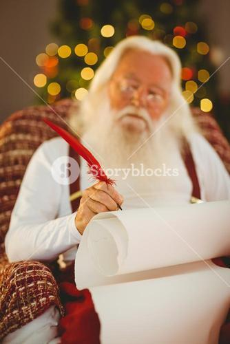 Concentrated santa writing list on the armchair