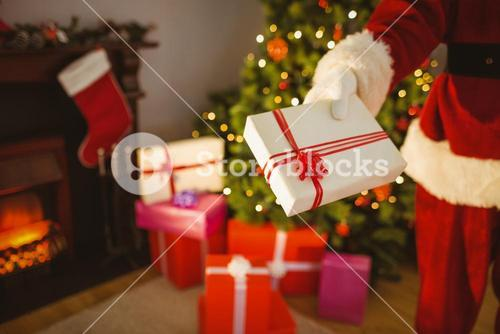 Mid section of santa delivering presents