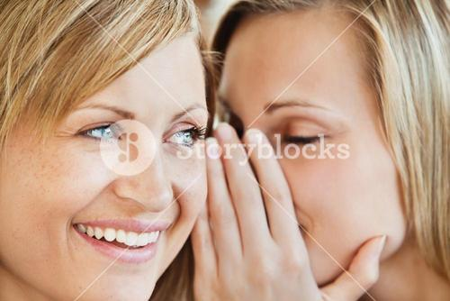 Blond young woman telling her friend a secret