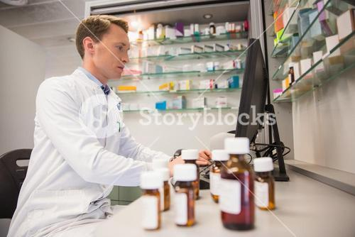 Pharmacist using computer at desk