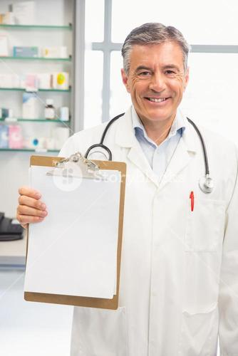 Happy pharmacist showing page on clipboard