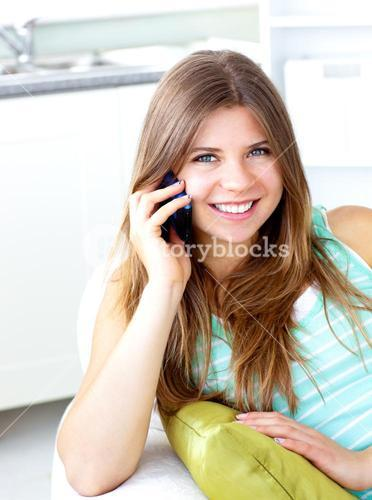 Positive woman talking on phone at home