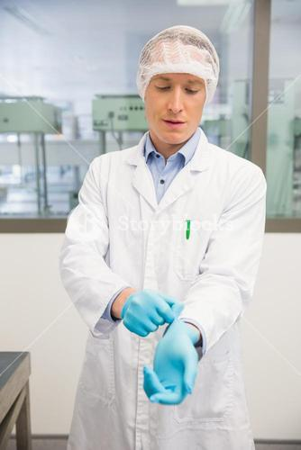 Pharmacist pulling on rubber gloves