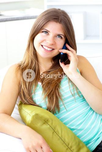 Glowing woman talking on phone at home sitting on a sofa