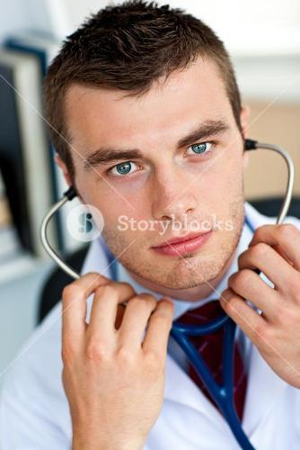 Confident male doctor holding a stethoscope in his office