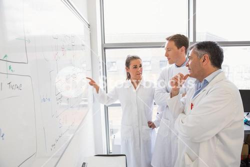 Science students and lecturer looking at whiteboard