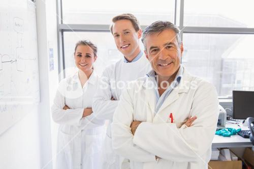Science students and lecturer smiling at camera