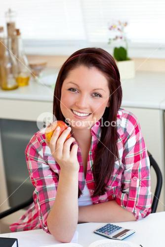 Delighted woman holding an apple sitting in the kitchen