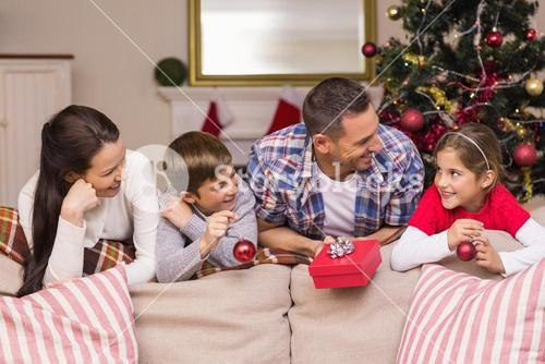 Smiling family leaning on the couch