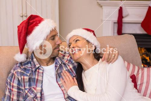 Smiling couple cuddling on the couch