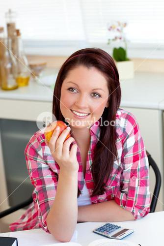 Radiant woman holding an apple sitting in the kitchen