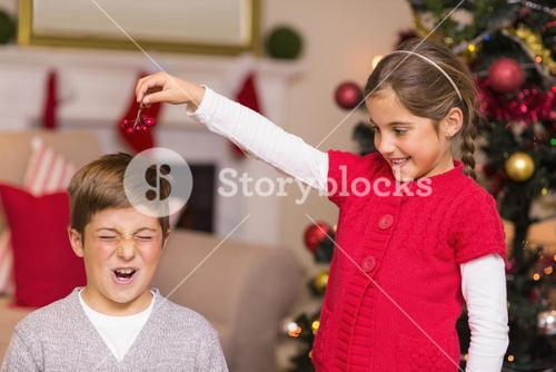 Little girl holding berries above brothers head